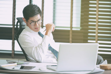 Businessman working at office with laptop.Toned image