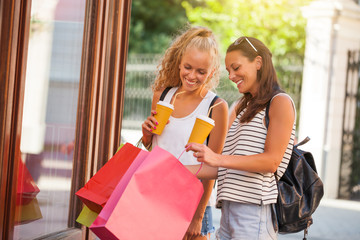 Two happy women are shopping in the city.