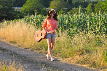 Beautiful Girl Alone Walking On The Country Road. Romantic Girl Traveling With Her Guitar