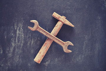 Rusty like crossed wrench and hammer made of chocolate on a dark slate background, color toning applied.