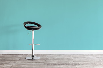Black bar stool in front of wall.