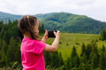 Little girl takes pictures in the mountains, she is traveling photographer.
