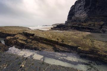 Black rocks in a wet beach
