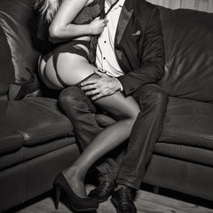 Rich man with lover in underwear on sofa black and white