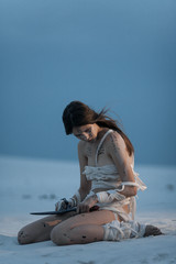Girl in image of Egyptian mummy sits on sand with knife in her hand.