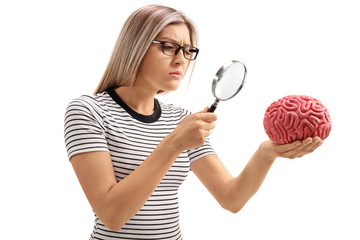 Young woman examining a brain model with a magnifying glass