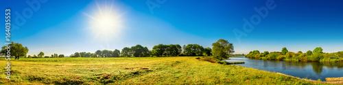 Wall mural Landschaft im Sommer mit Bäumen, Wiesen, Fluss und Sonne