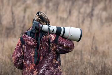 Animal Photographer. Photo Hunter. A Man In Camouflage Uniform With A Black Camera And A Large White Lens. A Man With A Camera On His Shoulder