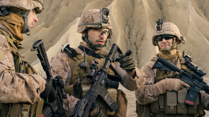 Shot of Fully Equipped Group of Soldiers Planning Their Actions Before Military Operation in the Desert.
