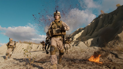 Shot of Fully Equipped Soldier Running Away From the Explosion. His Squad is Being Attacked and Bombed During Combat in the Desert.
