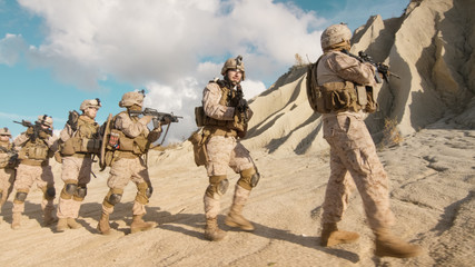 Squad of Fully Equipped and Armed Soldiers Walking in Single File in the Desert.