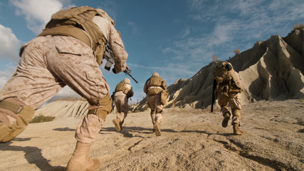 Close-up Shot of Squad of Soldiers Running Forward and Atacking Enemy During Military Operation in the Desert.