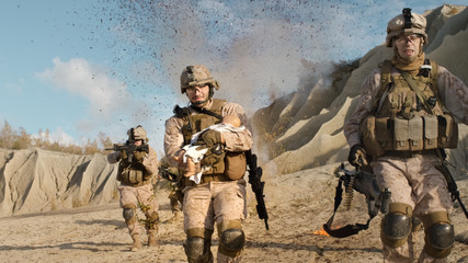 Soldier Running away from Explosions behind Carrying a Baby. While other Members of the Squad Covering Them During Battle in the Desert.