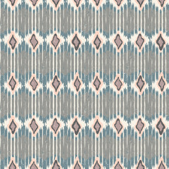 Vector seamless geometric pattern with chevron stripes in ikat fabric style.