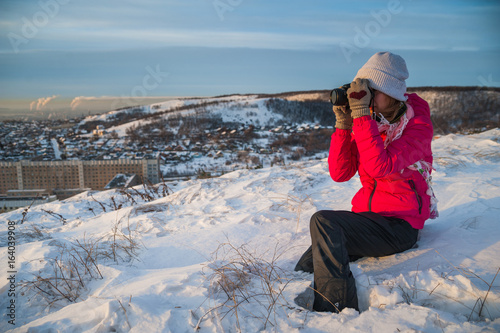 0972031c6 Girl tourist in a red jacket photographs the winter landscape on the ...