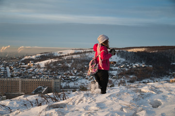 Girl tourist in a red jacket photographs the winter landscape on the camera. The tourist takes a picture of the dawn in the morning. A girl in a gray hat takes a picture of the morning city Saratov