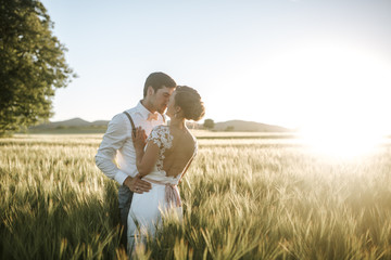 bride and groom standing in a field with sundown