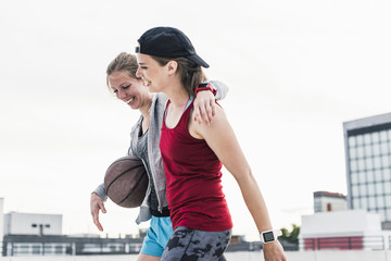 Two happy women with basketball in the city
