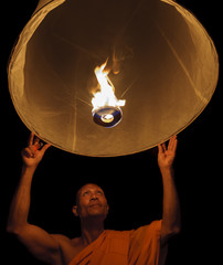 Thailand, Chiang Mai, Buddhist monk lighting lantern