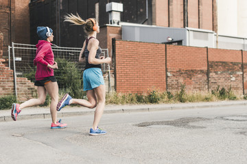 Two women running on the street along factory building