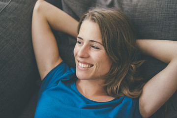 Smiling young woman lying on couch at home