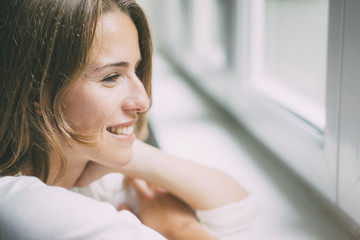 Smiling young woman looking out of the window