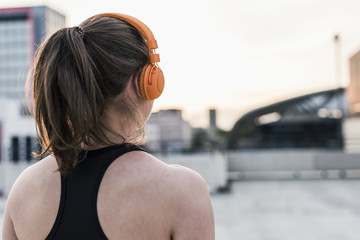 Active woman wearing headphones on parking level in the city