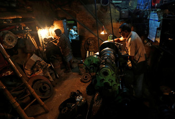 Workers operate lathe as they make spare parts of drilling machines at a workshop in Kolkata