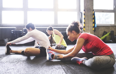 Three young people stretching in gym