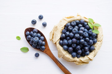 Fresh  blueberries in a cup and a spoon on a white surface of a table. Closeup, top view.