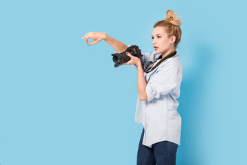 Woman blonde photographer shows how to pose to somebody. Model isolated on a blue background with copy space