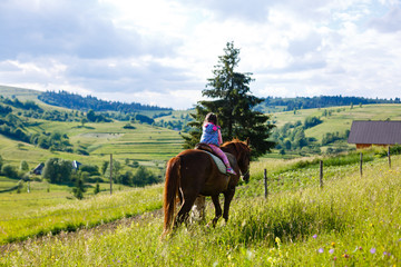 Lovely equestrian - little girl is riding a horse, mountain in the background