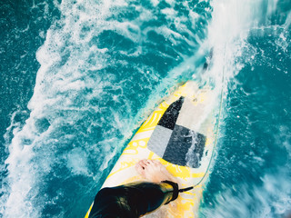 Surfer ride on yellow surfboard ride on wave. Surfing in blue ocean