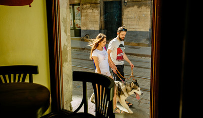 A lovely hipster couple with alaskan malamute dog walking in the street on summer time. in sunny morning. Shooting through the window of a cafe. Family, pet, animal and people concept.