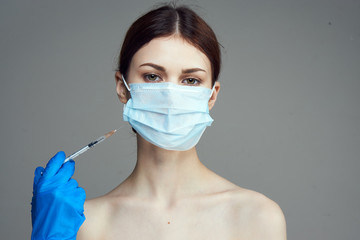 Fototapeta Beautiful young woman on a gray background holds a syringe, medicine, plastic