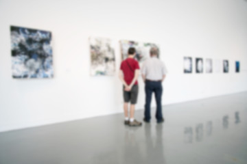 Blurry background of art gallery with people pay attention with the image on the wall.