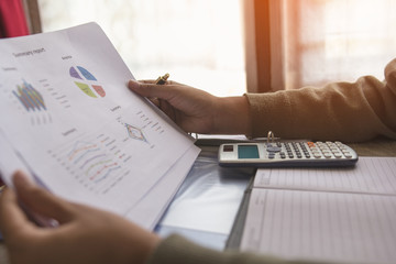 Businessman or accountant or banker making calculations and re check financial reports are set of documents prepared by an administrative team at the end of an accounting period. Concept finance