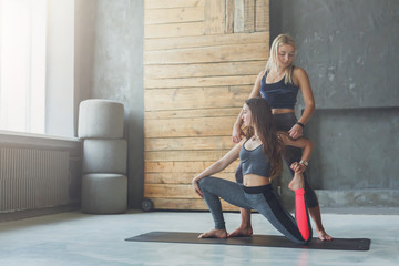 Young woman with yoga instructor in fitness club, mermaid pose