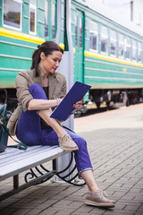 beautiful woman traveler taking notes in a notebook