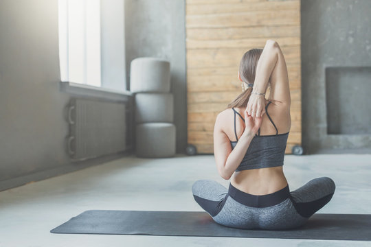 Young woman in yoga class, back stretching