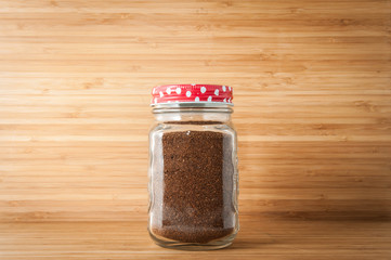 Coffee powder in glass bottle on wooden table.