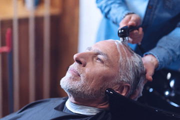 Delighted elderly man having his hair washed