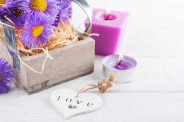 Purple daisies and lit candles on white table