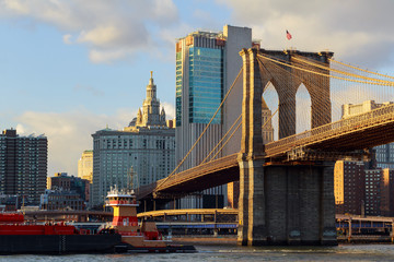 The Brooklyn Bridge stands against blue sky downtown Manhattan skyscrapers