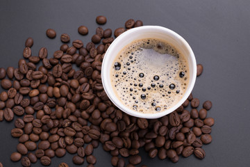 Hot americano coffee in paper cup of coffee and coffee beans on black background