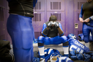 A football player sitting in a thoughtful state inside locker room