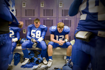 Texas high school football players deep in thought, in locker room, before the championship game.