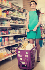 Woman with shopping cart standing in the supermarket