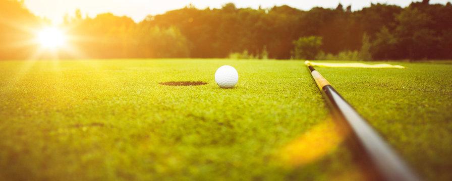 Golfplatz im Abendrot mit Loch und Golfball und Fahne