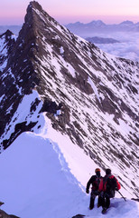 Foto op Aluminium Alpinisme mountain guide leads a client over a narrow and exposed snow ridge towards a rocky summit in the Swiss Alps near Zermatt at sunrise